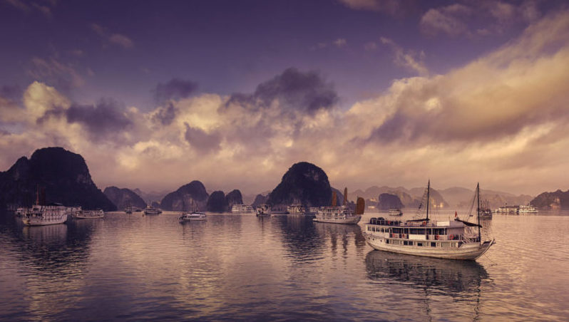 Tour and cruise boats among the karst formations in Halong Bay, Vietnam.