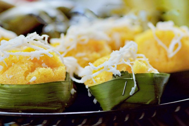 Authentic Banh Bo of An Giang is wrapped in a piece of banana leaf and served with fresh shredded coconut